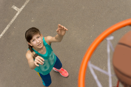 Athletic young girl scoring a goal in basketball as the ball enters the net, view from on top of the net as the ball passes through looking down on the girl photo