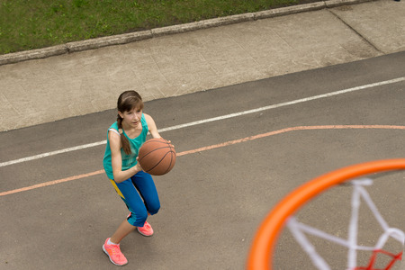 Teenage girl throwing a basketball at the net bending her knees as she prepares to launch herself into the air photo