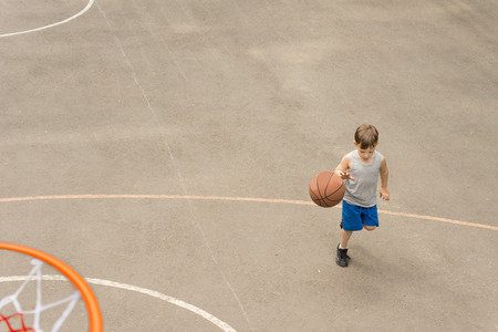 high angle view: High angle view from on top of the hoop of a sporty young boy playing basketball on an outdoor court running with the ball