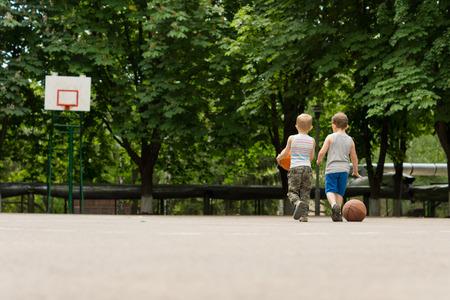 緑豊かな緑の木々 に裏打ちされた遠い goalpost に向かって一緒にバスケット ボール コートの上を歩く 2 人の若い男の子の後ろからビュー