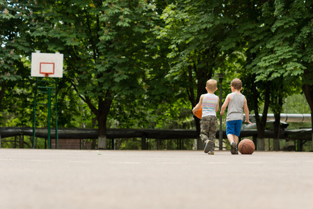 View from behind of two young boys walking across a basketball court together towards a distant goalpost backed by leafy green trees Stock Photo