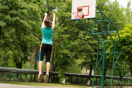 Jugador joven atl�tico Skilled femenina de baloncesto disparar a un objetivo en un salto de tenis al aire libre en el aire mientras se lanza la pelota, vista desde atr�s