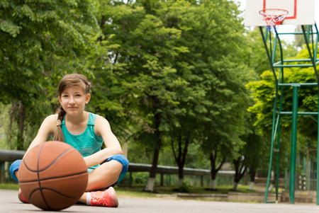 commence: Beautiful confident young female basketball player sitting cross-legged on the outdoor court surrounded by leafy green trees with the ball waiting for play to commence