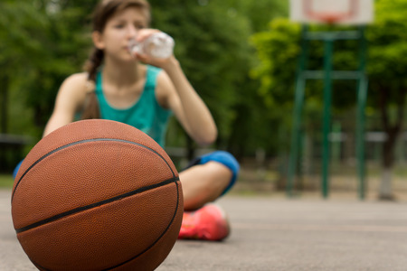 Young basketball player drinking water as she sits\ cross-legged on the court with the ball in front of her, focus to\ the ball