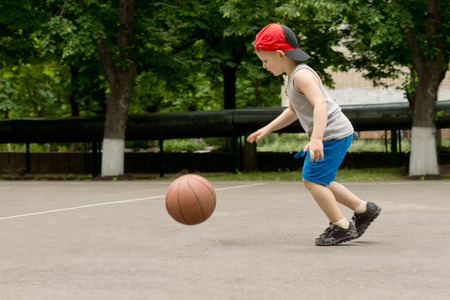 Small boy playing basketball running and bouncing the ball on a basketball court as he practices controlling the ball during the game