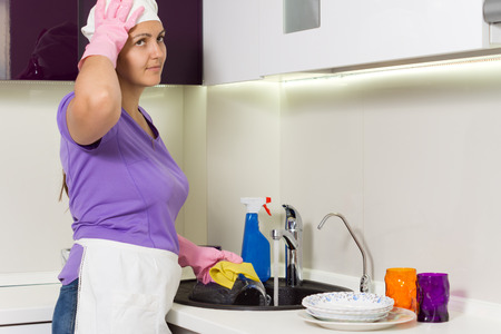 Housewife straightening her cap as she works in the kitchen washing the dishes in the sink photo