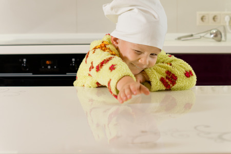 toweling: Young child in a yellow toweling gown and chefs hat stretching across a kitchen counter trying desperately to reach something that is out of reach