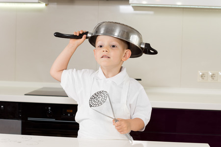 clowning: Little boy in a white apron clowning around with kitchen utensils standing with a saucepan upended on his head and a ladle in his hand