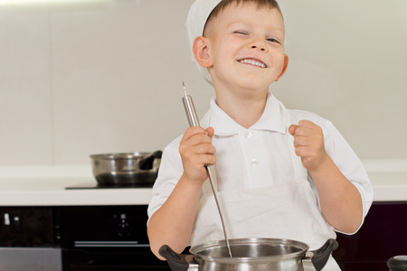 Happy young boy in a chefs toque enjoying cooking stirring the pot and cheering while punching the air with his other fist