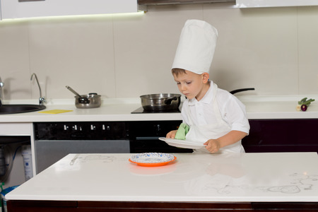 Small little boy in a chefs uniform wiping dishes and carefully placing them on the kitchen counter to be used in his baking