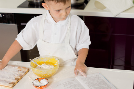 checking ingredients: Young boy cook checking ingredients in a recipe book as he adds them to the mixing bowl while baking in the kitchen