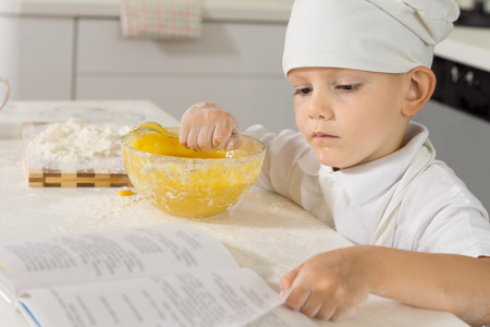 cook book: Little boy chef in a chefs uniform checking his recipe in a book as he bakes at the kitchen counter with eggs and flour