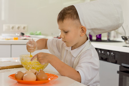 Cute young boy chef in a white toque standing at a kitchen counter whipping the eggs in the mixing bowl