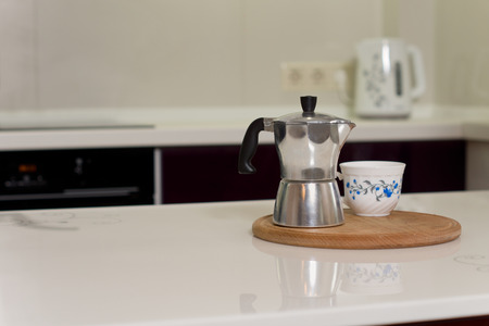 percolator: Coffee percolator and cup on a wooden board on a kitchen counter ready to serve a delicious freshly percolated brew, with copyspace