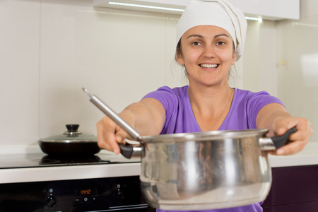 checking ingredients: Smiling woman in the kitchen holding out cooking pot