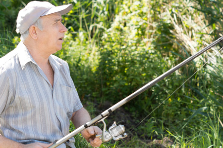 spinning reel: Elderly man fishing with a rod and spinning reel against a lush background of greenery and reeds, side view