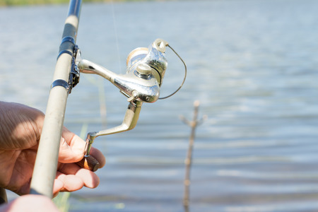 spinning reel: Fisherman using a spinning reel for freshwater fishing on a rural lake, close up of his hands and the reel