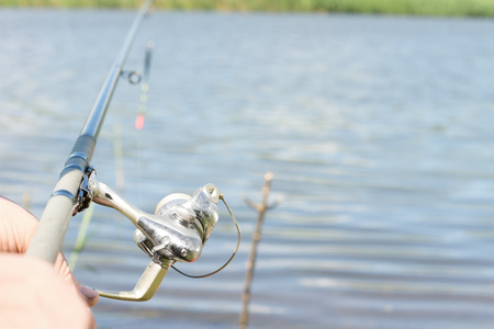 spinning reel: Angler fishing with a rod and spinning reel on a freshwater lake , view along the length of the rod Stock Photo