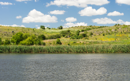 Beautiful tranquil scenic lake fringed with reeds backed by rolling green hills under a sunny blue sky with fluffy white clouds photo