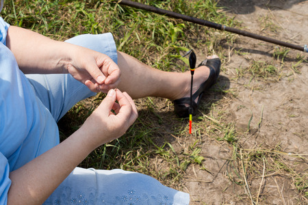 threading: Close up view of the hands of a woman threading bait onto her hook while fishing on the shore of a freshwater lake