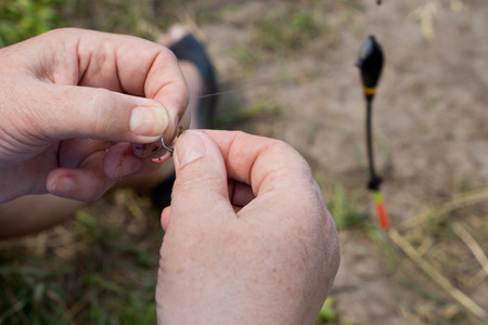 attaching: Woman attaching a new hook to a fishing line, close up view of her hands