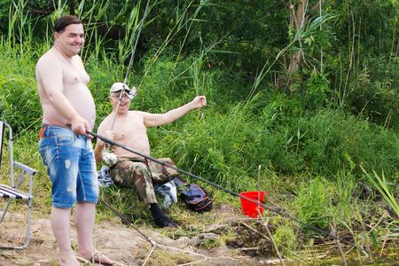 hombres sin camisa: Dos hombres sin camisa disfrutando de unos d�as de pesca desde la orilla de un lago o de un r�o con sus ca�as y carretes