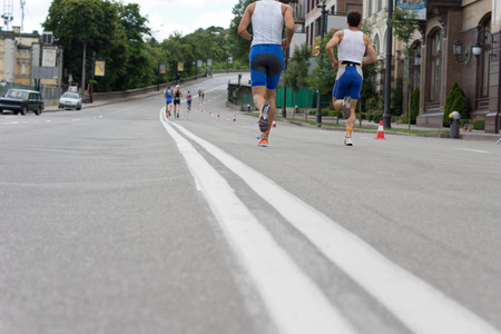 Low angle view of the legs of departing runners competing in an urban marathon or race running along a street lined with buildings