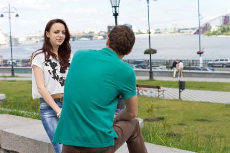 questioned: Attractive trendy young girl sitting on a stone wall chatting to her boyfriend overlooking a river in the background