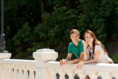 Happy young couple leaning on a white cement balustrade in front of leafy greenery as they give the camera a friendly smile, with copyspace Stock Photo - 29744042