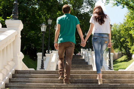 Affectionate young couple walking away from the camera up a flight of steps in a park shaded by trees holding hands