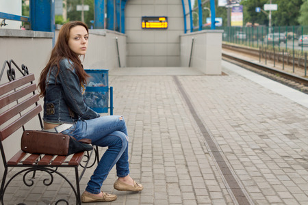 observant: Young woman sitting on a wooden bench waiting at a railway station for transport with a serious expression on a deserted platform