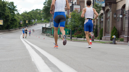 Competitors in a marathon or road race running along an asphalt road through a town , low angle view of their legs at street level Stock Photo