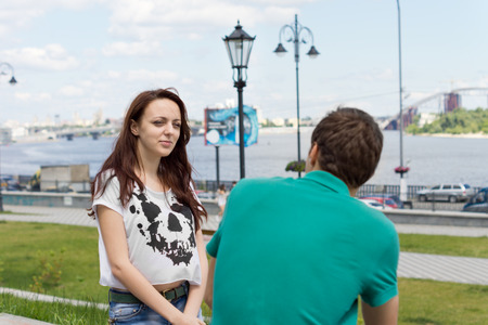 acquaintance: Smiling fashionable young woman with long brunette hair sitting on a wall chatting to a male friend with an urban river and highway in the background Stock Photo
