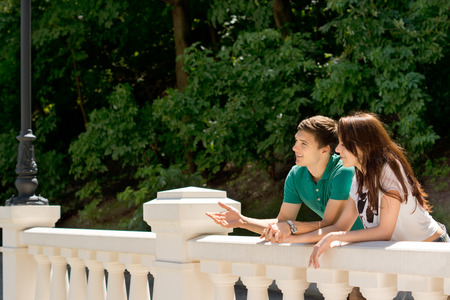Young couple standing chatting on a bridge leaning over the white cement parapet gesticulating as they look out over the view against a background of leafy greenery Stock Photo - 29744241