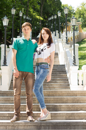 Trendy young couple posing on a steep flight of stairs in an outdoor park leading back up a steep hillside standing arm in arm photo