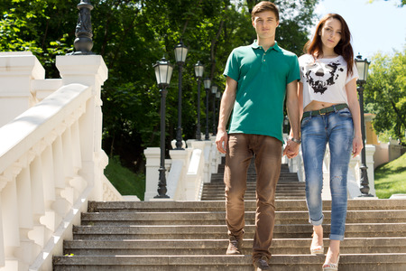 Romantic young couple holding hands walking down a steep flight of stairs shaded by leafy green trees in a park approaching the camera, low angle view photo
