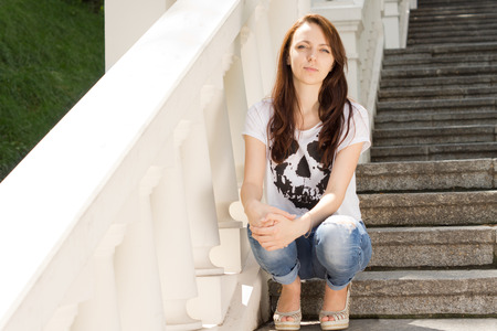 unemotional: Attractive young woman sitting on a steep flight of steps with a painted white balustrade clasping her knee with her hand looking at the camera with a serious expression