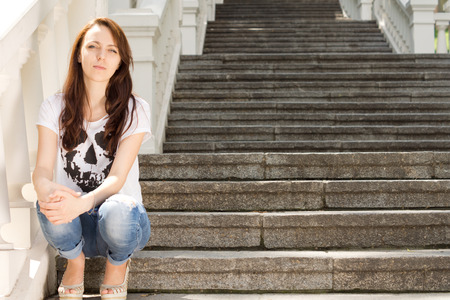 unemotional: Lonely young woman sitting on a step on an open-air staircase disappearing up into the distance staring quietly at the camera with a serious expression