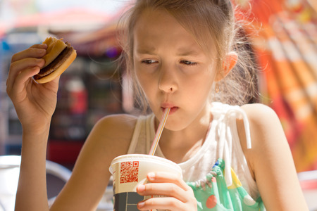 Portrait of a contemporary cute little girl drinking with a straw a sweet cold beverage from a soda cup, while holding a hamburger, in a fast-food restaurant, in summer