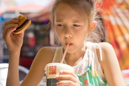 alimentos y bebidas: Retrato de una ni�a linda contempor�nea beber con una pajita una bebida fr�a dulce de una taza de soda, mientras que la celebraci�n de una hamburguesa en un restaurante de comida r�pida, en el verano