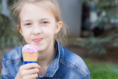 Pretty young girl enjoying an ice cream cone smiling at the camera as she enjoys a cool refreshing mouthful photo