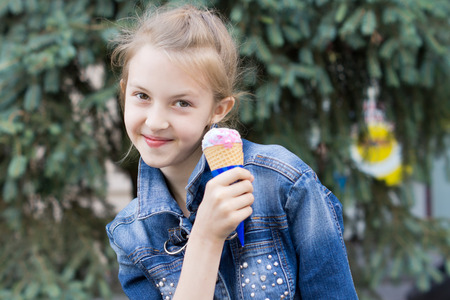 Playful attractive young girl eating ice cream grinning as she holds the cone of strawberry ice alongside her cheek on a sunny summer day outdoors photo