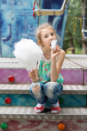 relishing: Young girl relishing a stick of candy floss munching on the sugary confection as she sits on a set of colorful steps in the summer sunshine