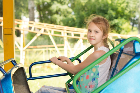 gripping bars: Smiling little girl sitting on a fairground ride gripping the colorful side bars as though not sure that she will enjoy the speed with an expression of trepidation Stock Photo