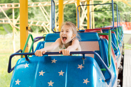 Adorable funny little girl screaming and holding on, while experiencing the adrenaline rush of a ride in the roller coaster, in an amusement park, in summer