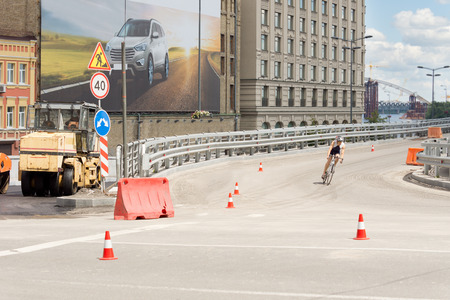 Cyclist corning off an urban overpass at speed riding past traffic warning cones and a barricade blocking a tarring machine and roadworks Stock Photo