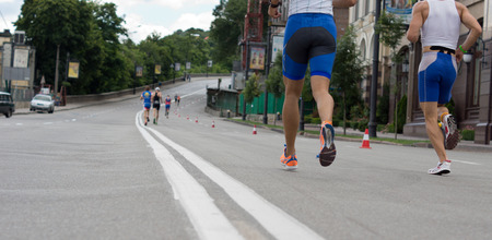 entrants: Low angle view of the legs of runners in an urban road race running down a street past parked vehicles and buildings Stock Photo