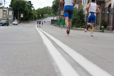 Low angle view from tarmac level of the legs of a group of road runners in a race running along an urban road past buildings and parked cars Stock Photo