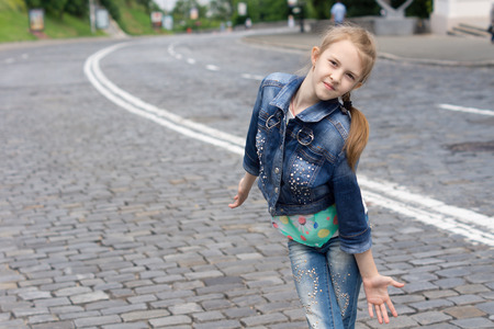 Funny fashionable little blond girl wearing trendy denim jacket and blue jeans while posing as a top model outdoors, on a cobblestone street