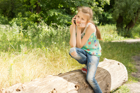 sitting area: Bored girl, wearing blue jeans while sitting on a log, having a call on the mobile phone, in a sunny green area, in the countryside